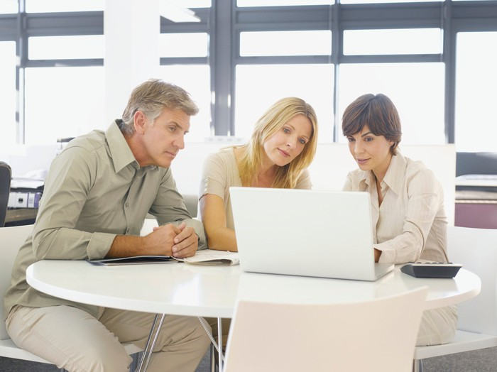 Older couple working with a financial advisor looking at a laptop
