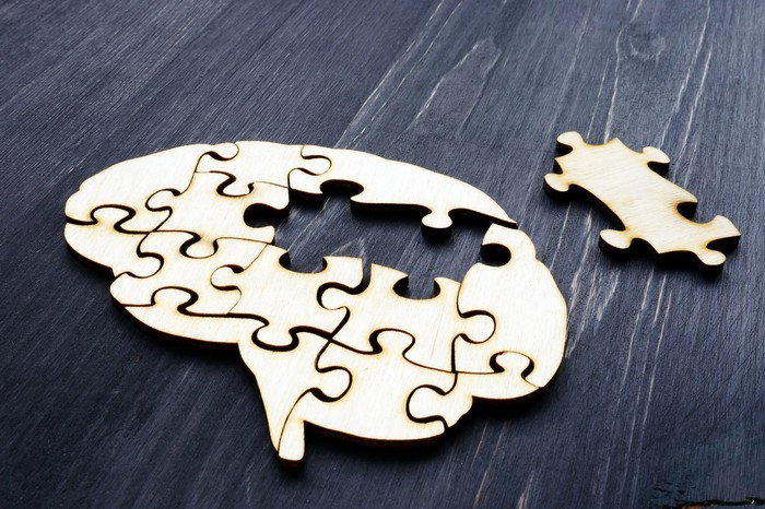 A gold metallic puzzle of the brain with a center piece missing and set aside.