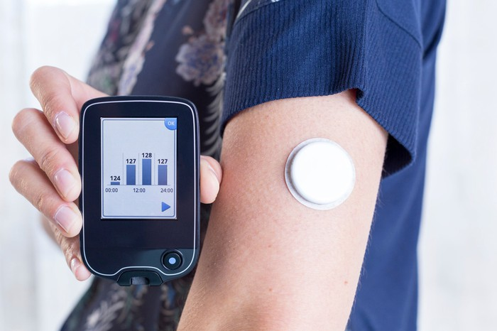 Diabetes patient with continuous glucose monitor on their arm and a handheld reader.
