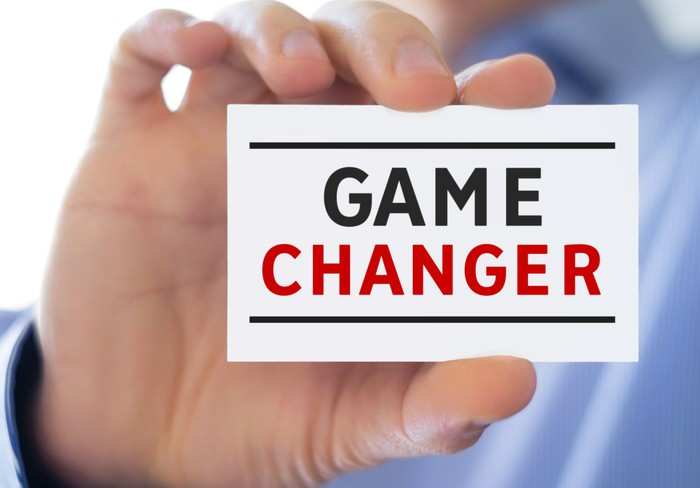 An investor holds up a business card with the words game changer written on it.