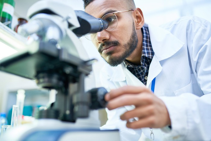 Male lab technician wearing glasses and a white lab coat peers into microscope in foreground.