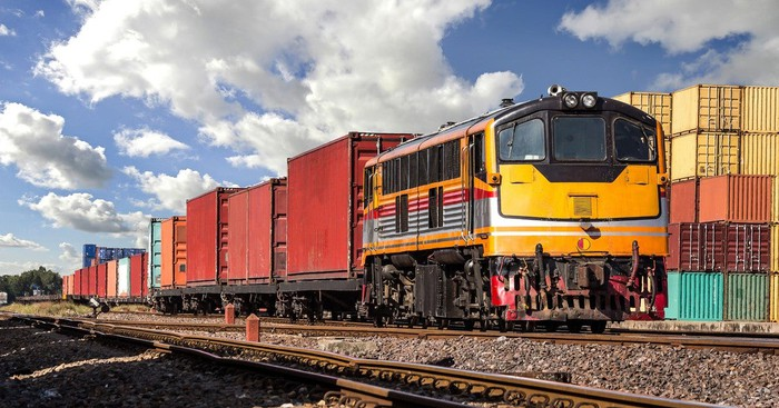 Train on a track with containers alongside.