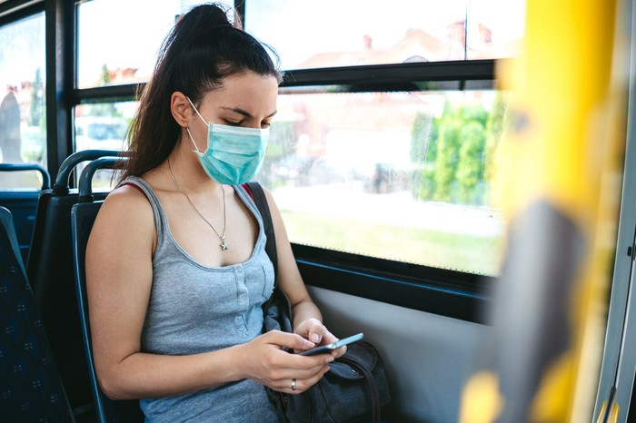 A young woman on a bus wearing a surgical mask and looking at a phone