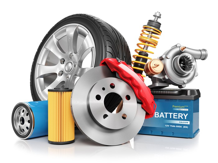 A collection of auto parts, including a tire, a shock absorber, and a battery.