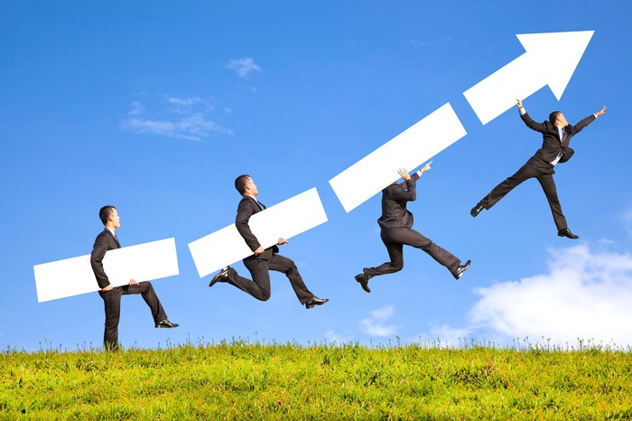 Four businessmen are carried progressively higher by pieces of a rising arrow.