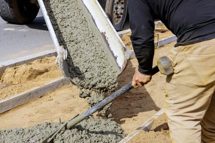 A Construction worker dispersing cement from a cement truck.