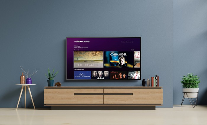 A flatscreen TV mounted on a wall displaying The Roku Channel, with sideboard, a side table, and a potted plant nearby