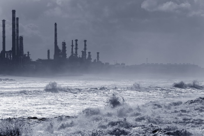 A storm hitting an oil refinery by the sea.