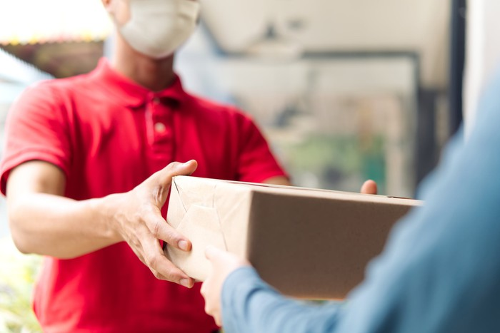 A masked deliveryman hands a package to  a customer at  their doorstep.