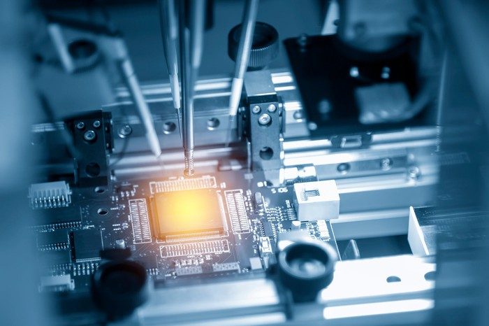 Inner workings of a machine that produces an illuminated square semiconductor chip.