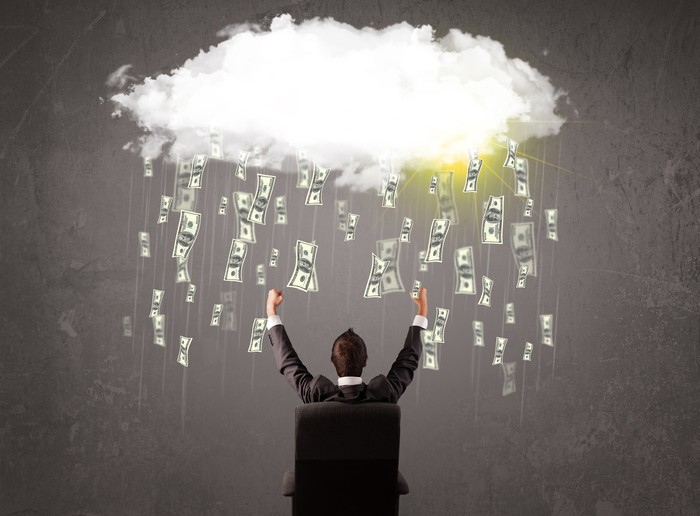 Businessman in suit looking at cloud with falling bills