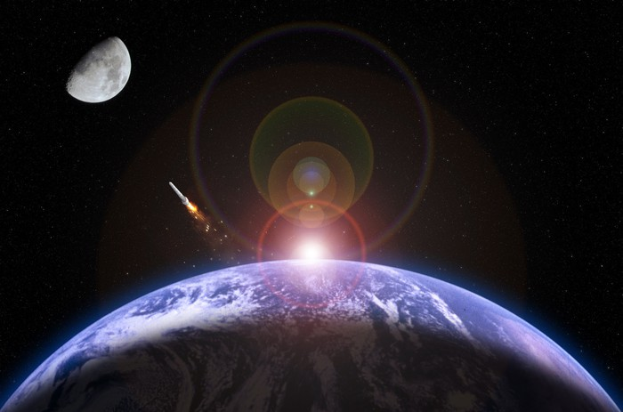 Sunrise over Earth and a rocket launching to the moon