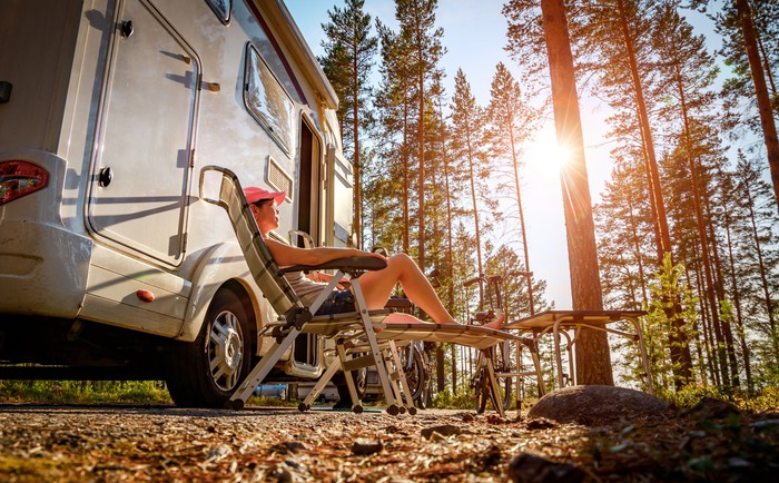 People sitting in lawn chairs outside a motor home in a sunlit pine forest.