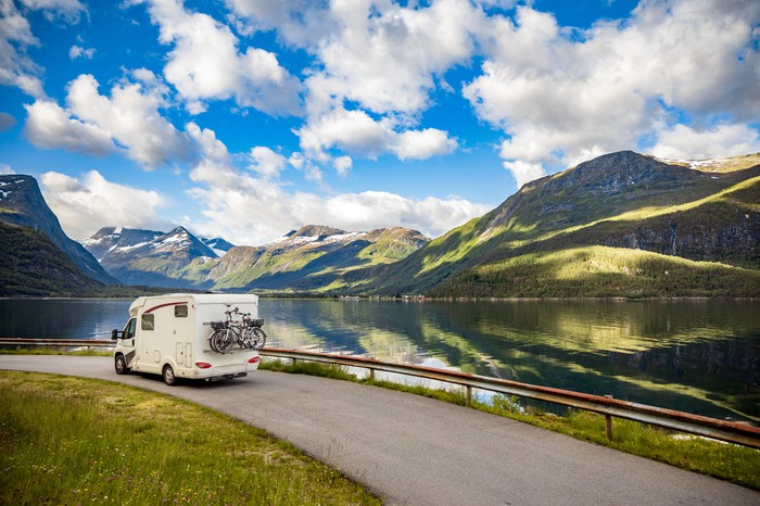 An RV driving along a road next to a lake, with hills and a partly cloudy sky in the background.