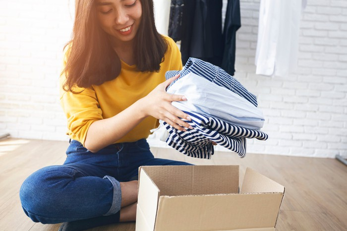 A young woman takes clothing from a delivery box.