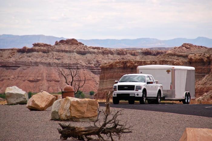Ford truck in desert landscape.