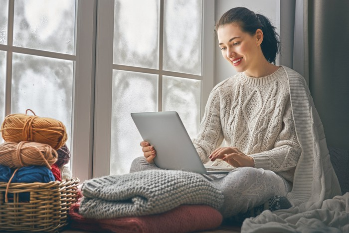 Woman using laptop while sitting by a window.