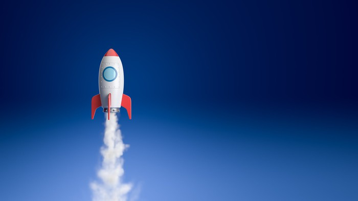 A toy rocket blasts off in front of a blue background.