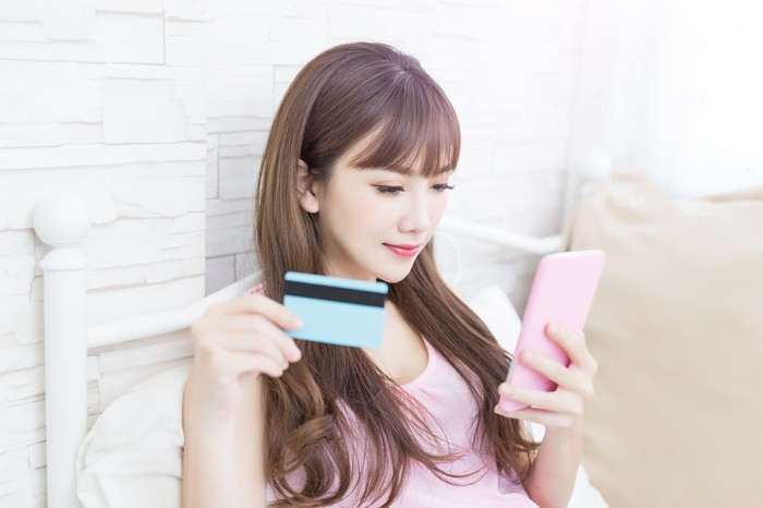 A young woman looking at a smartphone while holding a credit card.