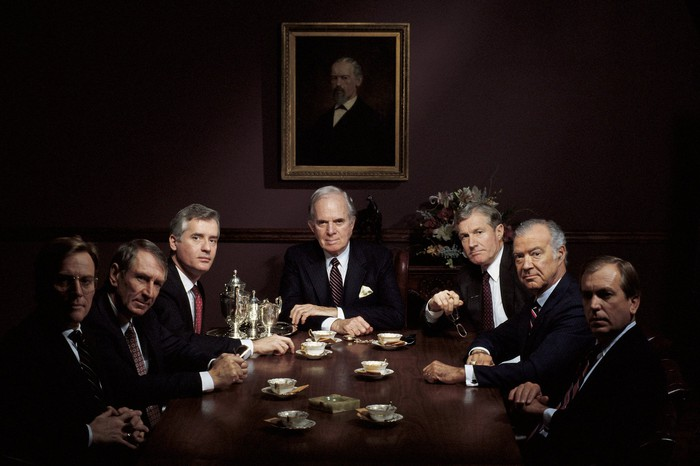 Men in suits sit around a wooden conference table in a dark room.