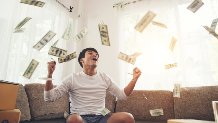 A man on a couch celebrates as money flies through the air around him.