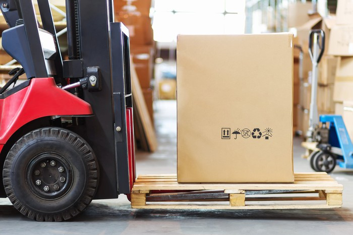 A red forklift moving a large box, possibly containing furniture, at a warehouse.