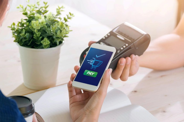 One person holding mobile phone with word Pay on screen, while another holds payment device.