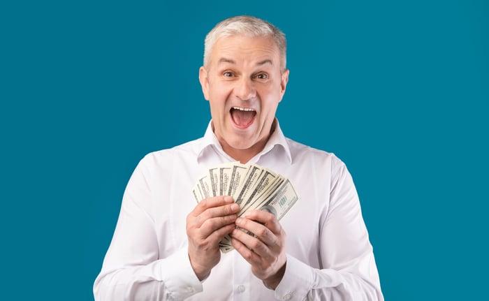Older man holding fanned-out hundred-dollar bills.