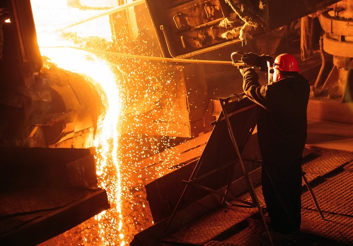 a steel worker in protective gear works with molten steel.