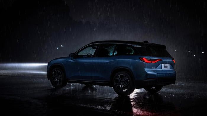 A NIO ES8 driving in the rain at night.