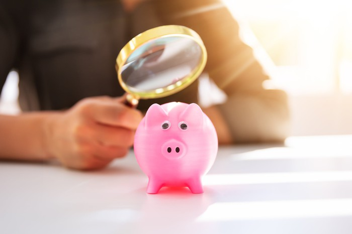 A businesswoman uses a magnifying glass to look at a pink piggy bank