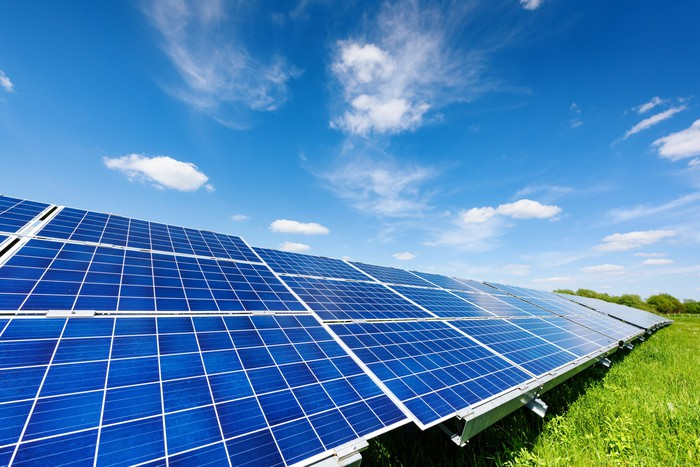 Solar panels in a green field with a bright blue sky.