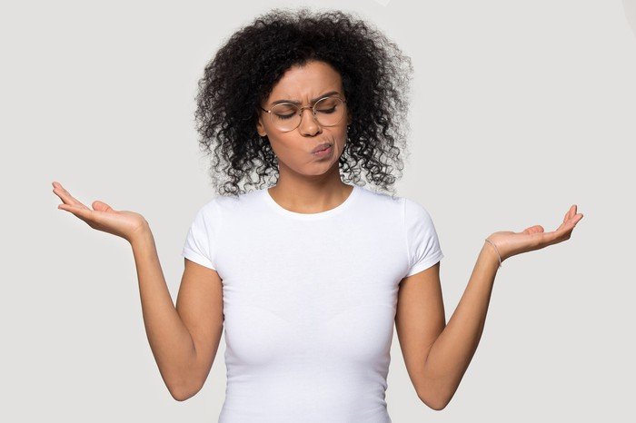 A woman holding up her palms and looking like she's weighing her options.