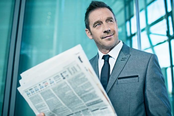 A smirking businessman holding a financial newspaper.