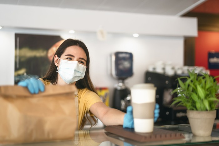 A woman in a mask and gloves serving coffee and holding a bag.
