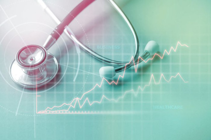 A stethoscope is superimposed over a rising stock chart.