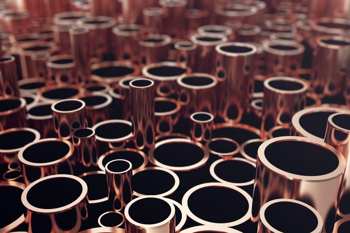 A large collection of copper pipes sitting on their ends.