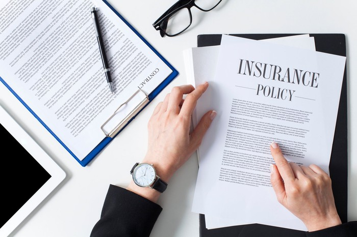 An overhead shot of a person at a desk with an insurance policy laid out in front of them