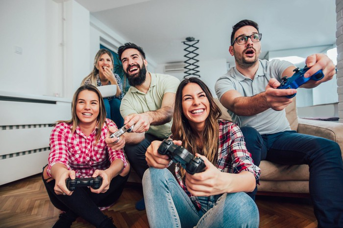 A group of young adults plays a video game.