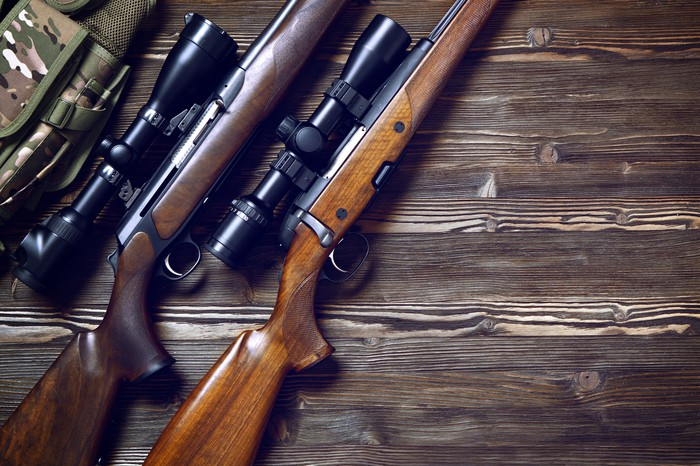 A pair of guns with scopes on a wood table.