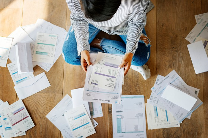 Man surrounded by a pile of bills.