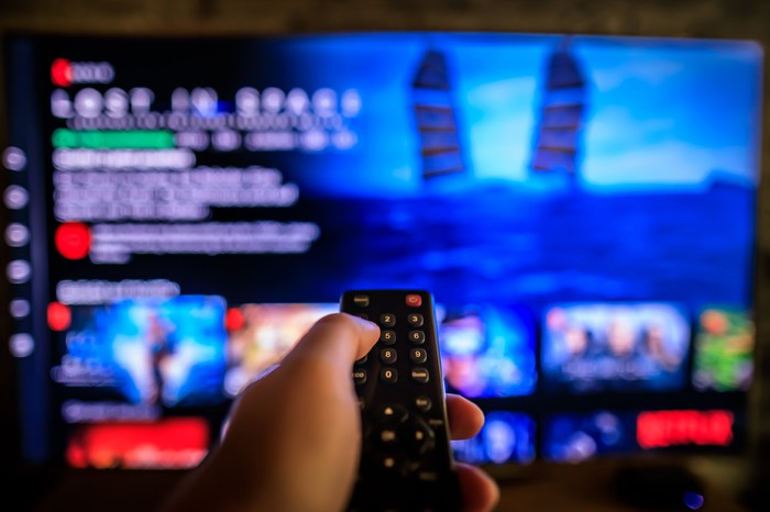 left hand holding remote watching a streaming service on TV