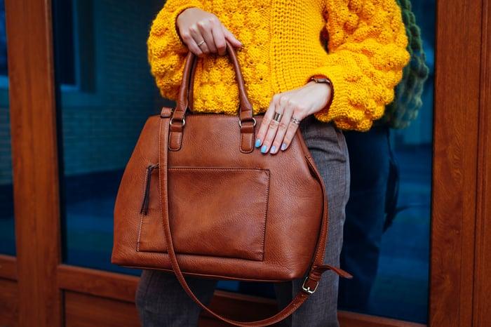 Lady wearing yellow sweater and holding large handbag