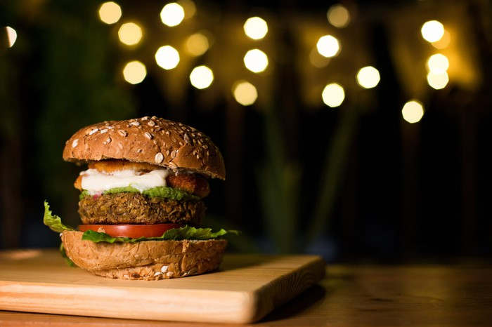 Plant-based burger sitting on a wooden board