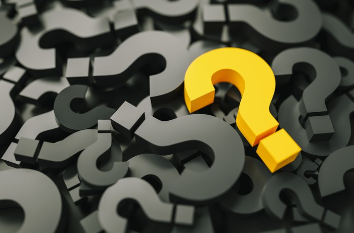 Dozens of question marks in a pile, with one in yellow on top