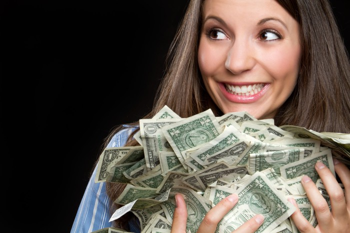 A smiling woman holds an armful of dollar bills