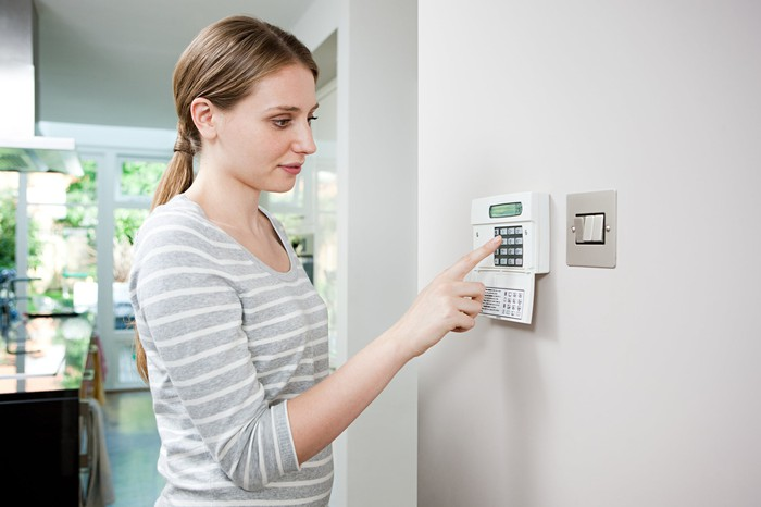A home owner adjusts her thermostat.