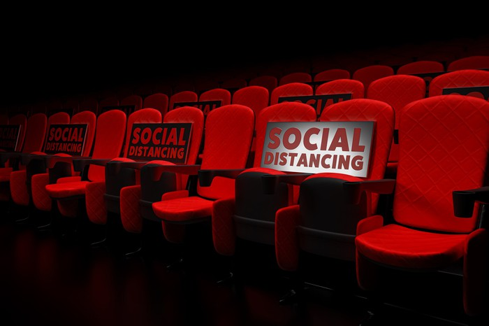 Movie theater seats with social distancing signs on them