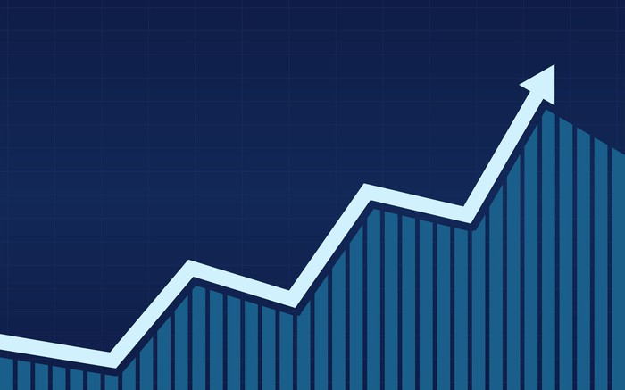 A white line graph rising on top of a blue bar chart