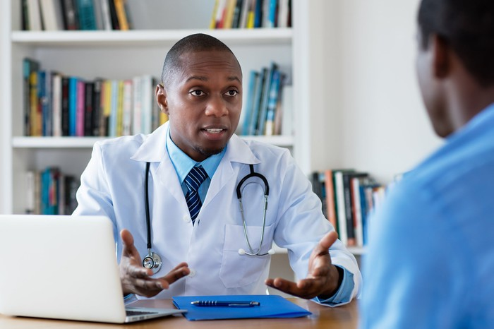 Doctor at a desk talking to a patient.